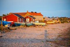 渔船和钓鱼在日落光的海滩在瑞典 免版税库存照片