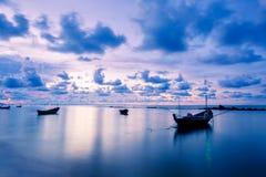 渔船在完全风平浪静浇灌象与云彩的玻璃在天空,在日出期间被采取的长的曝光 免版税库存照片