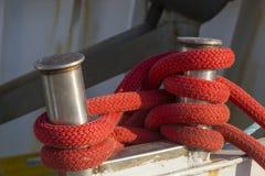 渔船在港口-有红色绳索的系船柱 免版税图库摄影