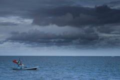 渔船在黑暗天空和风暴来的海漂浮 免版税库存照片