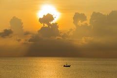渔船现出轮廓和海水波纹在日出期间在泰国 免版税库存照片