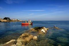 渔船通过岩石 免版税库存图片