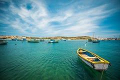 渔船临近Marsaxlokk村庄  图库摄影