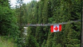 温哥华,加拿大:旅游业- Capilano有加拿大旗子的吊桥 库存图片