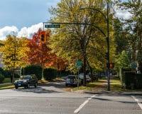 温哥华,加拿大- 2017年10月1日:第12条大道和灰街道的交叉点在一晴朗的秋天天上色了树 免版税库存图片