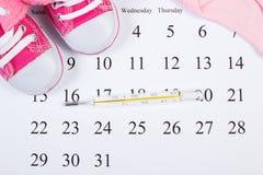 温度计和衣物新出生的在日历,期望为婴孩 免版税图库摄影
