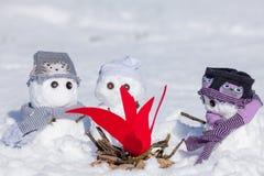 温暖三个逗人喜爱的雪人保持 免版税库存照片