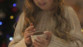 温暖与杯子的冬天毛线衣的女孩热的茶,等候圣诞节 股票录像