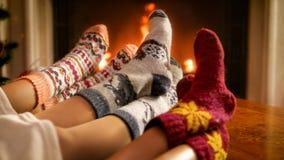 温暖他们的脚的家庭的图象在灼烧的壁炉在客厅 免版税库存照片