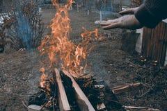 温暖他的手的白种人人在冷的黑暗的大气的营火 免版税库存照片