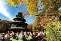 温暖和晴朗的秋天天气导致了拥挤啤酒庭院在中国塔在慕尼黑 库存图片