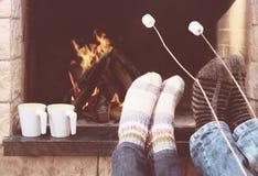 温暖在壁炉的夫妇的脚 库存图片