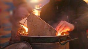 温暖在有火的大大桶前面的人们,设法得到在篝火附近温暖了 股票视频