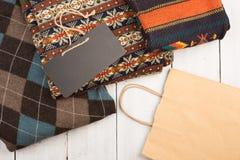 温暖在木架子的被编织的毛线衣 套有另外装饰品、购物袋和牌的冬天套头衫 免版税库存照片