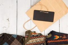 温暖在木架子的被编织的毛线衣 套有另外装饰品、购物袋和牌的冬天套头衫 免版税库存图片