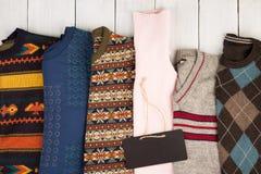 温暖在木架子的被编织的毛线衣 套有另外装饰品和牌的冬天套头衫 库存图片