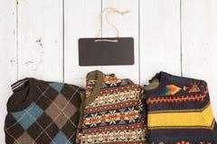 温暖在木架子的被编织的毛线衣 套有另外装饰品和牌的冬天套头衫 免版税图库摄影
