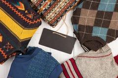 温暖在木架子的被编织的毛线衣 套有另外装饰品和牌的冬天套头衫 库存照片
