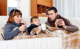 温暖在温暖的calorifer附近的结冰的父母和十几岁的儿子 免版税库存图片