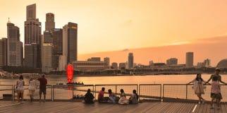 温暖在现代大厦的五颜六色的在小游艇船坞海湾沙子的日落和建筑学与放松在船坞和观看的地平线的人 免版税库存照片