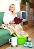 温暖她的脚的微笑的妇女 免版税库存照片