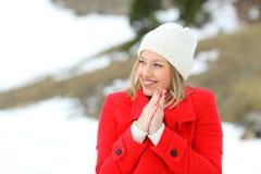 温暖愉快的妇女保留在一座多雪的山 库存图片