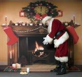 温暖由壁炉的圣诞老人 免版税库存照片