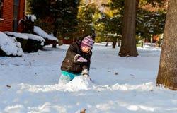 温暖的冬天成套装备的滑稽的小女孩,修造的雪人 使用的孩子户外  库存照片