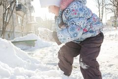 温暖的冬天衣物上升的随风飘飞的雪的小女孩 免版税库存照片