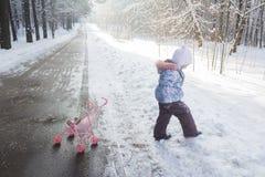 温暖的冬天衣物的走的小女孩在随风飘飞的雪中 库存图片