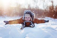 温暖的冬天衣裳的愉快的矮小的滑稽的男孩获得在雪爬犁的乐趣,户外在降雪期间 图库摄影