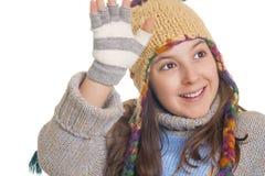 温暖的冬天衣裳的美丽的女孩微笑和挥动 免版税库存图片