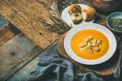 温暖的南瓜奶油色汤用油煎方型小面包片和种子,选择聚焦 图库摄影