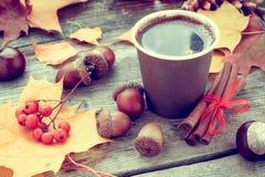 温暖的咖啡杯和秋天静物画在桌上 库存照片