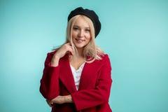 温暖的在蓝色背景隔绝的外套和盖帽的宜人的白肤金发的女孩 库存图片
