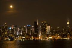 温暖的城市光在满月下的温暖的夜 免版税库存照片