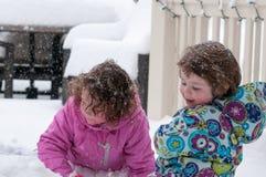 温暖的外套和被编织的帽子的愉快的小孩兄弟姐妹女孩扔雪和获得乐趣在冬天外面,室外 免版税图库摄影