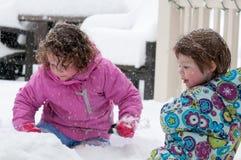 温暖的外套和被编织的帽子的愉快的小孩兄弟姐妹女孩扔雪和获得乐趣在冬天外面,室外 库存照片