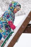 温暖的外套和被编织的帽子的愉快的小孩女孩扔雪和获得乐趣在冬天外面,室外画象 图库摄影