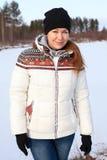 温暖的夹克的微笑的站立在冻湖附近的妇女,帽子和手套在冬天晒干 库存照片