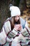 温暖的女孩有一杯茶的格子花呢披肩 免版税库存照片