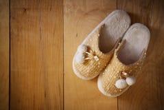 温暖的妇女拖鞋顶视图在木地板的 图库摄影