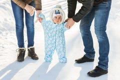 温暖的孩童用防雪装的男婴走在有的冬天公园的父母 第一个冬天和第一个小孩在雪跨步 库存图片
