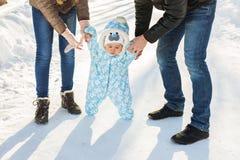 温暖的孩童用防雪装的男婴走在有的冬天公园的父母 第一个冬天和第一个小孩在雪跨步 免版税库存图片