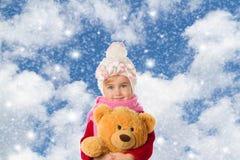 温暖的帽子和一件红色毛线衣的小女孩有玩具熊的 免版税库存图片