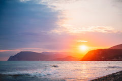 温暖的日落或日出在海洋和山 美好的颜色 免版税库存图片