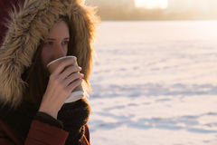 温暖的有外套和的敞篷的女孩一份热的饮料在一冷的天 图库摄影