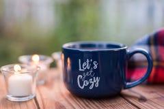 温暖的杯子和蜡烛外面在一秋天天 免版税库存图片