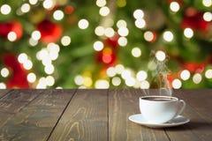 温暖的杯子在木桌面的无奶咖啡 作为背景的被弄脏的圣诞树 背景圣诞节关闭红色时间 库存照片