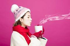 温暖的毛线衣的妇女喝一杯茶的 免版税库存照片